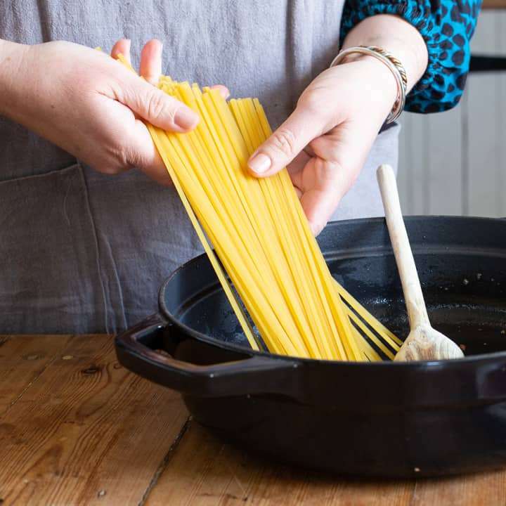 womans hands placing a handful of dried linguine pasta into a black cooking pot