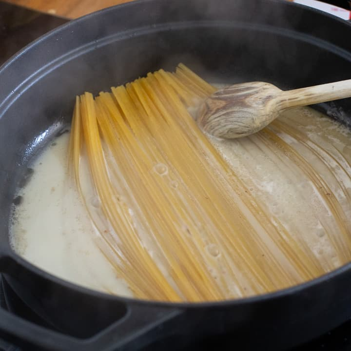 inside a black cooking pot with pasta cooking in a milky liquid
