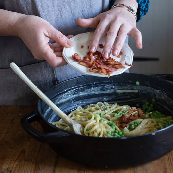 womns hands tipping crispy bacon pieces from a small white plate into a black pan of creamy pasta