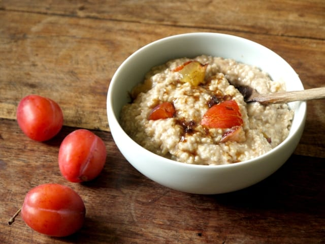 A white bowl of plum and cinnamon porridge with brown sugar sprinkled on top. on a wooden board with plums and a spoon