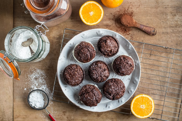 Chocolate Orange Muffins on a white plate surrounded by baking products
