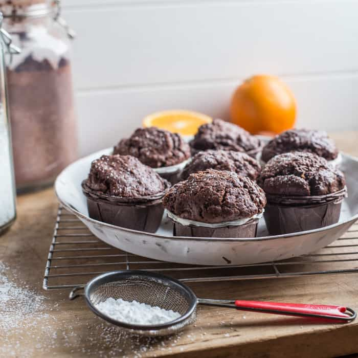 White plate with 7 chocolate orange muffins on, surrounded by baking items