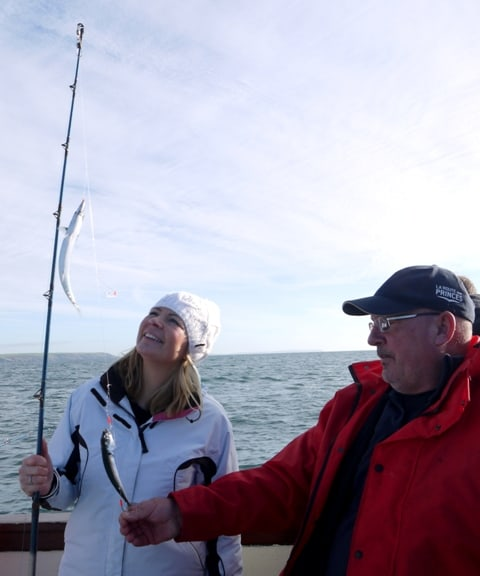 Jennie holding a fishing line with 2 mackerel