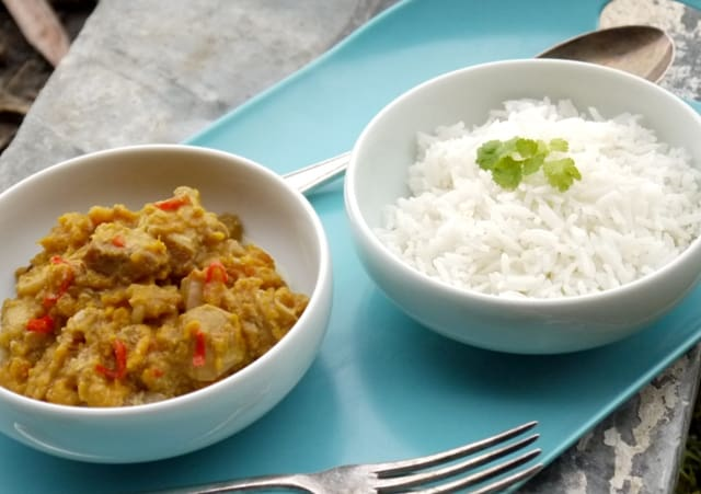 Slow Cooker Chicken and Sweet Potato Curry with Rice in white bowls on a blue tray with a fork