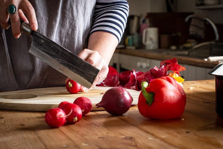 womans hands chopping radishes on a woodne board in a rustic kitchen setting