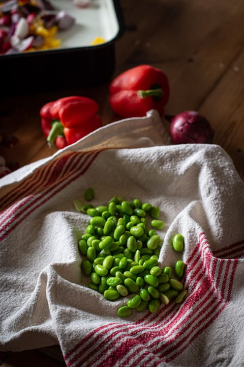 white and red cloth draining defrosted edamame beans in a rustic kitchen setting