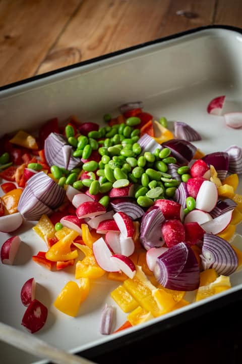inside of a large baking tin show brightly coloured vegetables about to be roasted