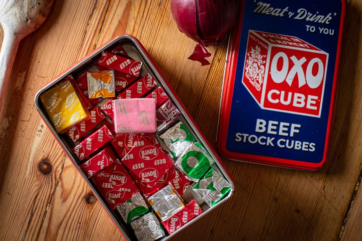 wooden kitchen counter with red OXO tin filled with various flavoured stock cubes