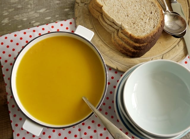 Honey Roast Root Veg Soup  in a soup pan beside soup bowls ,bread on a bread board and spoons on a red and white polka dot cloth