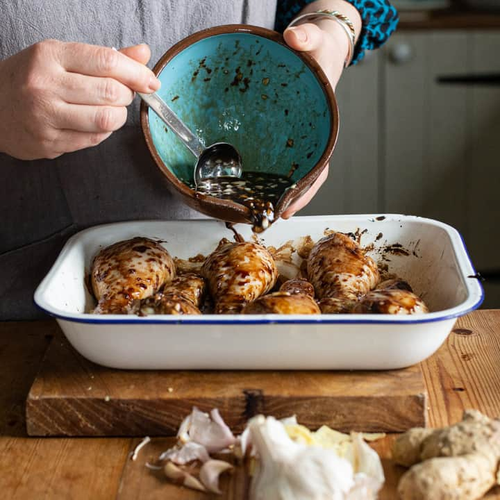 womans hands pouring a balsamic marinade from a blue bowl into a tray of chicken drumsticks