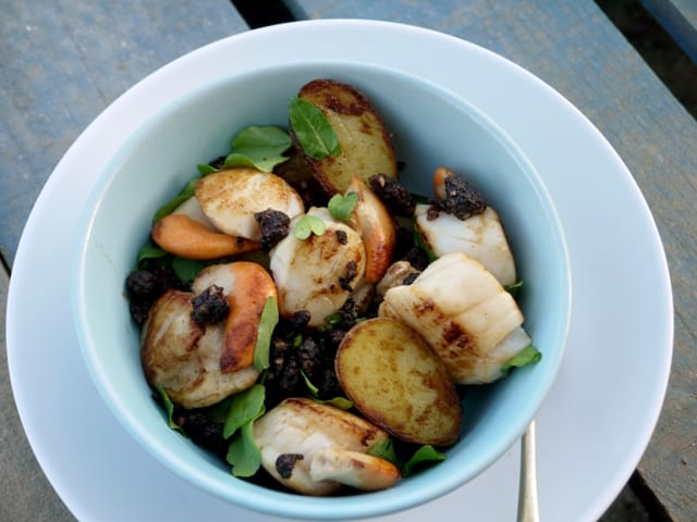 Scallops, New Potatoes and Crumbled Black Pudding in a white bowl