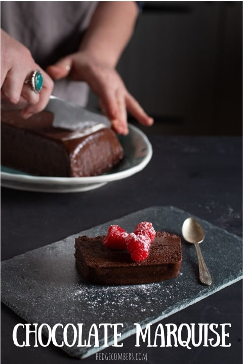 Slice of dark chocolate marquise cake on piece of slate with 3 raspberries and icing sugar on top