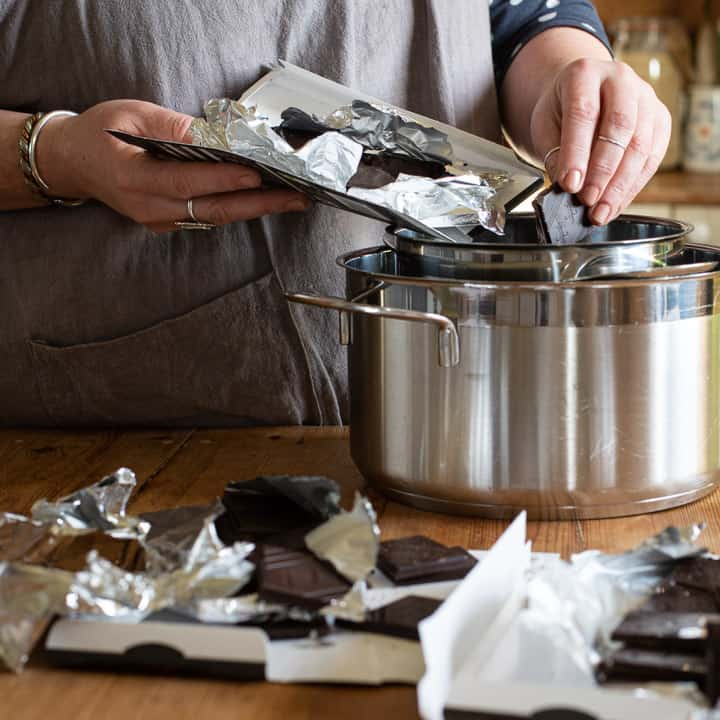 womans hands dropping broken pieces of dark chocolate into a silver saucepan