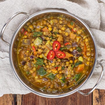 metal bowl of lentil curry on a wooden background