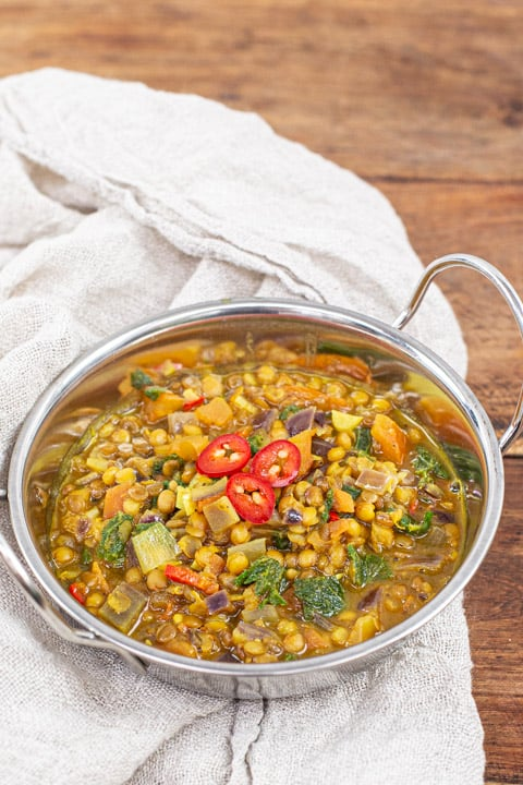 metal bowl of lentil and nettle curry on a wooden background