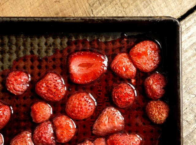 Pan of Hot Roast Strawberries on a wooden kitchen table top
