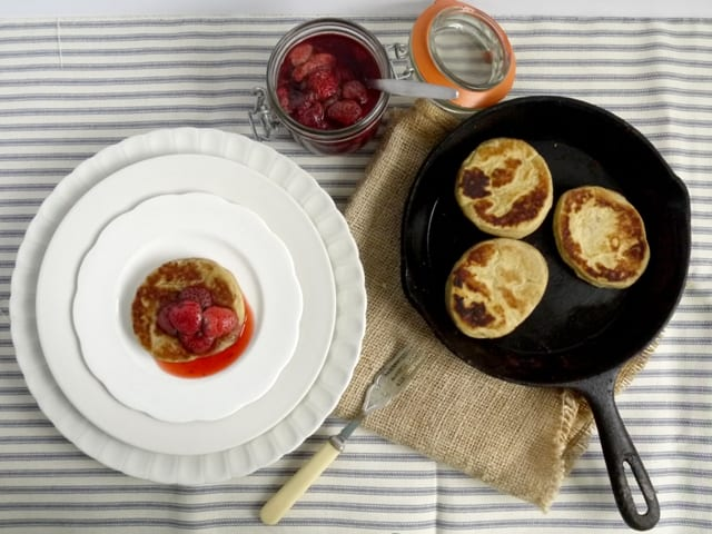 Hot Griddle Cakes with Roast Strawberries on white plates beside a kilner jar of roast strawbwrries and a pan of griddle cakes