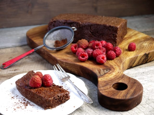 A wooden board with a French dessert called Chocolate Marquise and fresh raspberries on