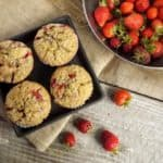 wooden surface with homemade muffins and strawberries on