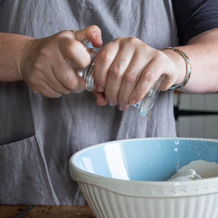 woman in grey grinding black pepper into a blue bowl of strawberry muffin batter