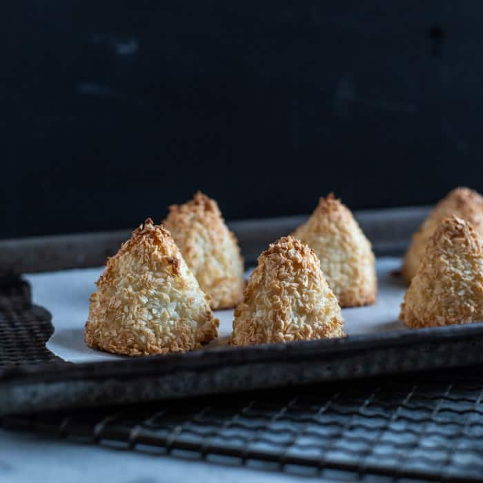 little golden coconut pyramid cakes on a baking sheet lined with baking paper