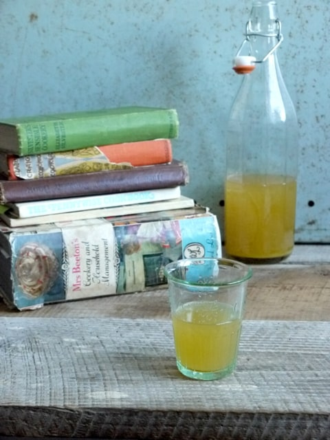 A bottle and glass of Royal Barley Water beside a pile of vintage cookbooks