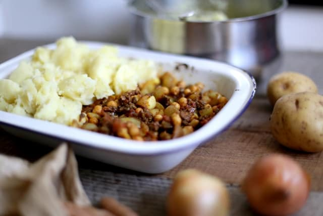 moroccan Shepherd's Pie in an enamel dish on a table surrounded by vegetables and cookware
