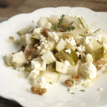 White plate with pear walnut and feta salad