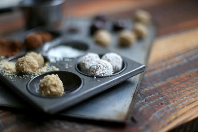 messy baking shot with handmade cookie dough truffles on a metal baking sheet with melted dark chocolate