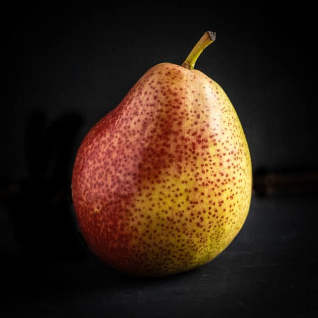 A perfect, ripe pear on a black background