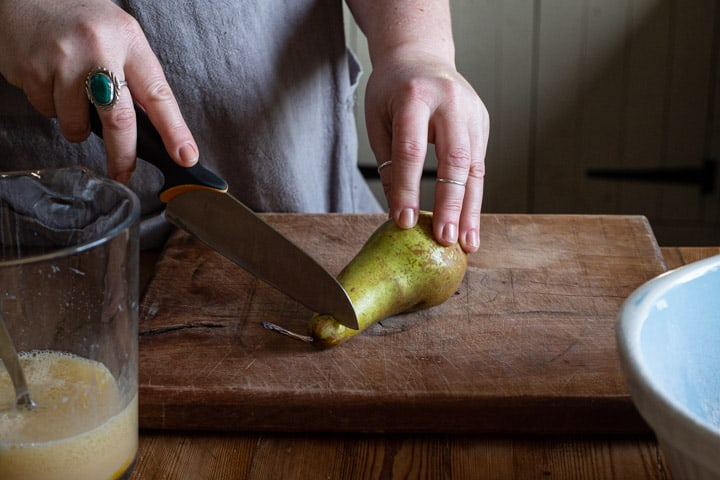 womans hands cutting up a green pear on a wooden chopping board
