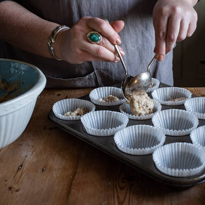 womans hands spooning pear muffin mixture into white paper muffin cases in a silver metal muffin tray