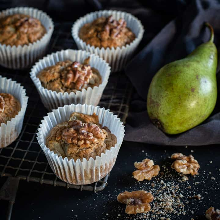 black background and 5 pear muffins on a rustic cooling rack with raw green pears and walnut halves scattered around