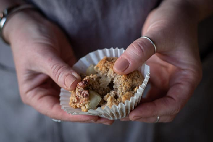 womans hands showing the moist inside of a spiced pear muffin