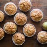 Wooden board with Spiced Pear Muffins and a fresh pear on