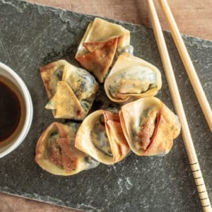6 crispy cooked vegetarian wontons served on a slate with chopsticks