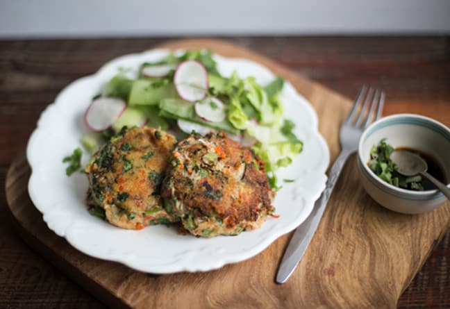 wooden chopping board with white plate holding crab cakes and green salad
