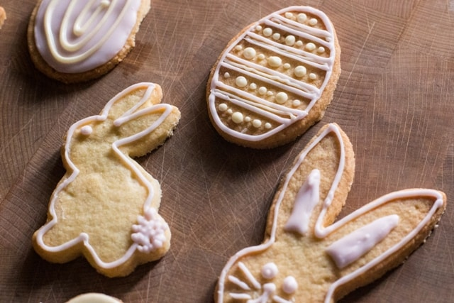 Dairy Free Easter cookies in the shape of rabbits, eggs and chicks, laid out on a wooden board