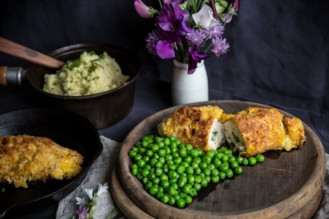 Wild Garlic Chicken Kiev on a wooden plate with green peas on a purple and lillac cloth with serving bowl of mashed potatoes and flowers in a vase