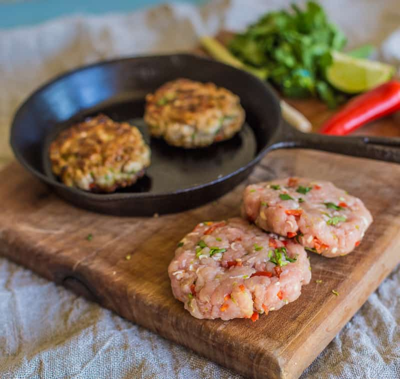 Turkey and Lemongrass Burger in a frying pan on a wooden table top surrounded by uncooked burgers ,chillis,lemongrass and lemon