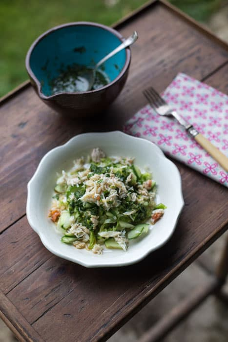 Small white bowl with Asian Crab Salad and a second bowl with a coriander dressing