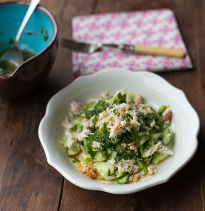 Small white bowl with Asian Crab Salad, a second bowl of coriander dressing and a pink napkin