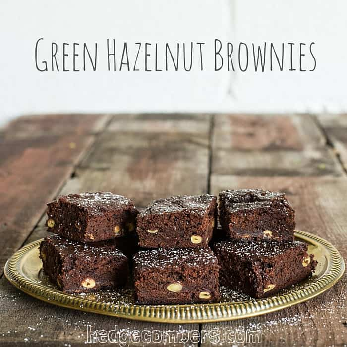 6 Green Hazelnut Brownies piled on a plate on a wooden table