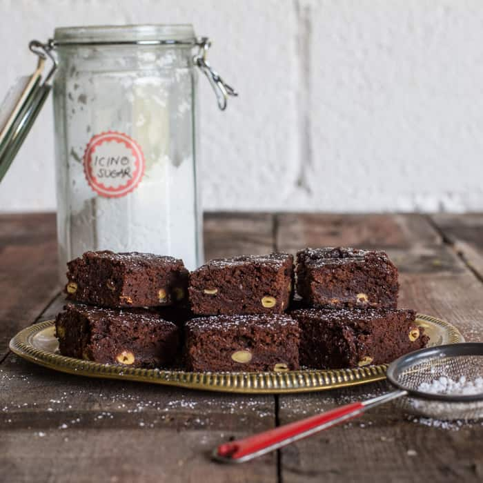 6 Green Hazelnut Brownies piled on a plate on a wooden table with a glass jar of icing sugar and a small sieve of icing sugar beside it