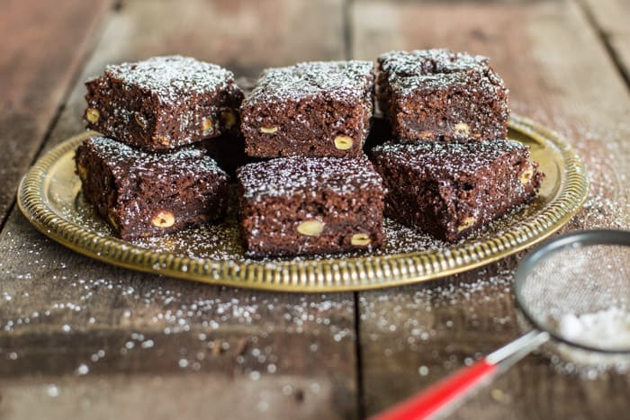 6 Green Hazelnut Brownies piled on a plate on a wooden table with a small sieve of icing sugar