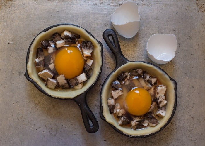 shortcrust pastry lined pans with mushrooms and an egg in eacch for Mini Breakfast Pies