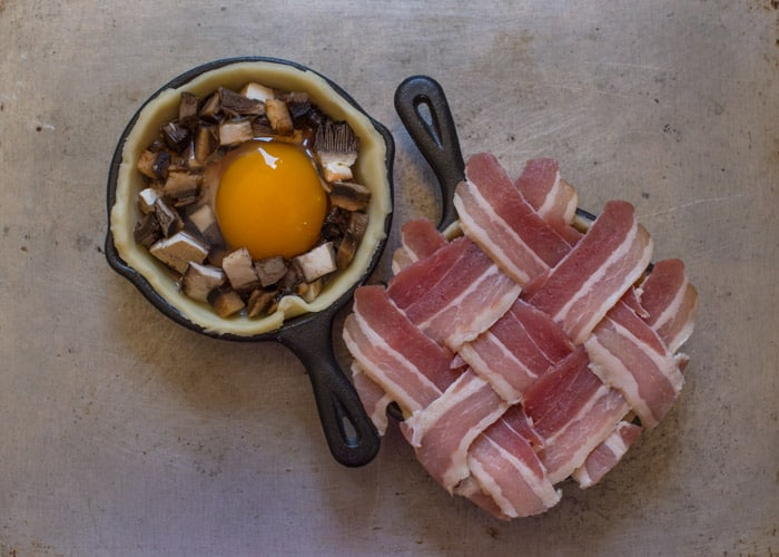 Mini Breakfast Pies being prepared in small cast iron pans covered in a bacon lattice