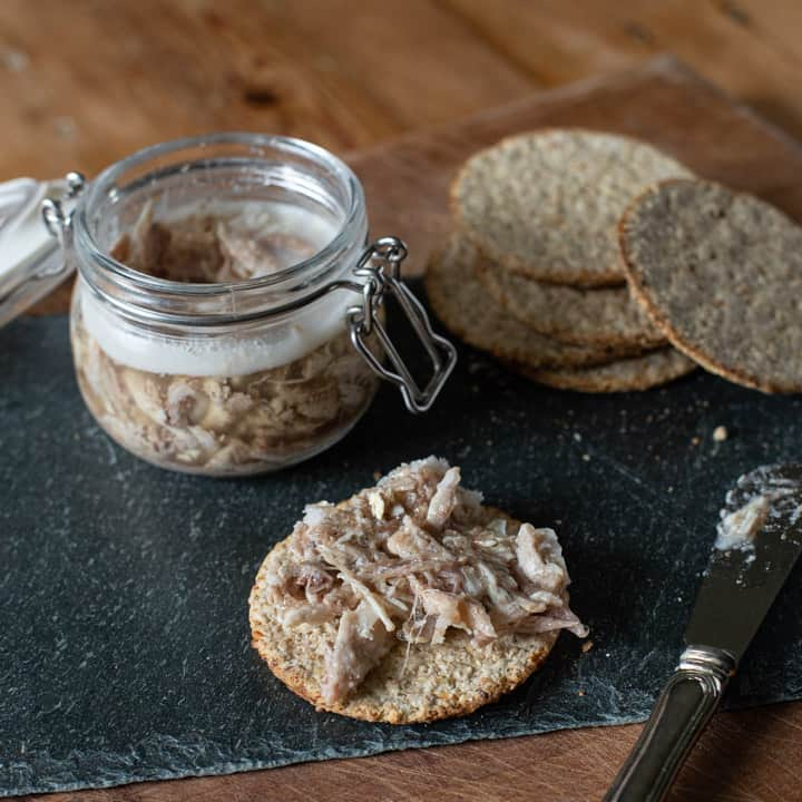 wooden board with glass jar of rabbit terrine, oat cakes and a small silver knife