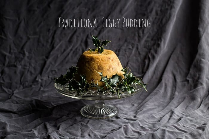 Glass dish with traditional figgy pudding surrounded by holly against a black background