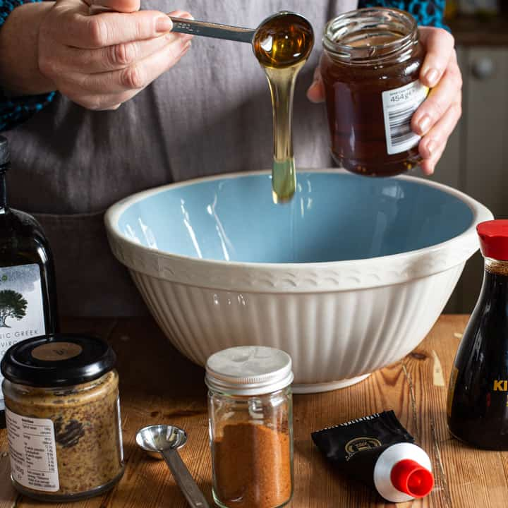 womans hands drizzling a silver spoon of honey into a large blue and white mixing bowl